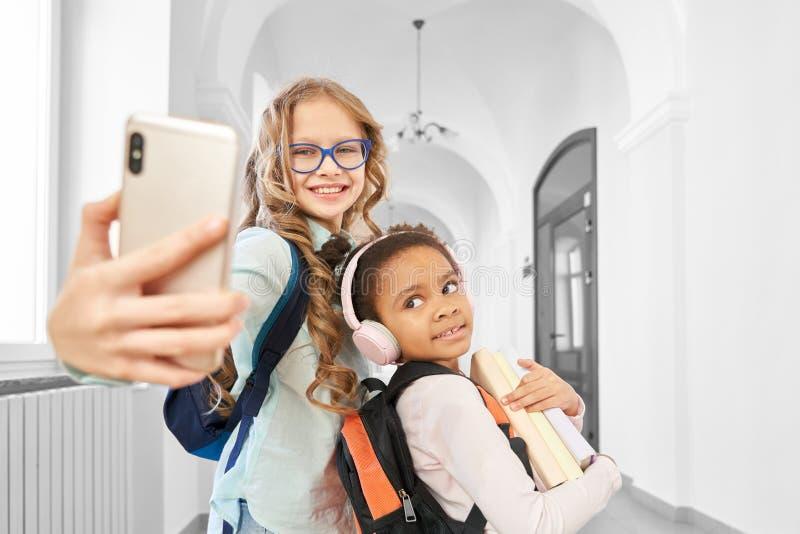 Amigos engra?ados da escola que fazem o selfie no corredor da escola fotografia de stock royalty free