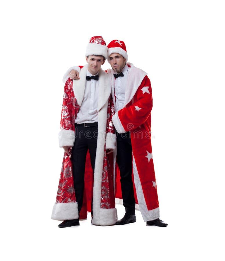 Amigos engraçados que levantam nos revestimentos de Santa Claus imagens de stock