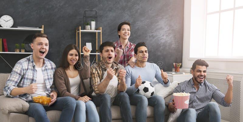 Amigos entusiasmado que olham o f?sforo de futebol e que comem a pipoca em casa fotos de stock