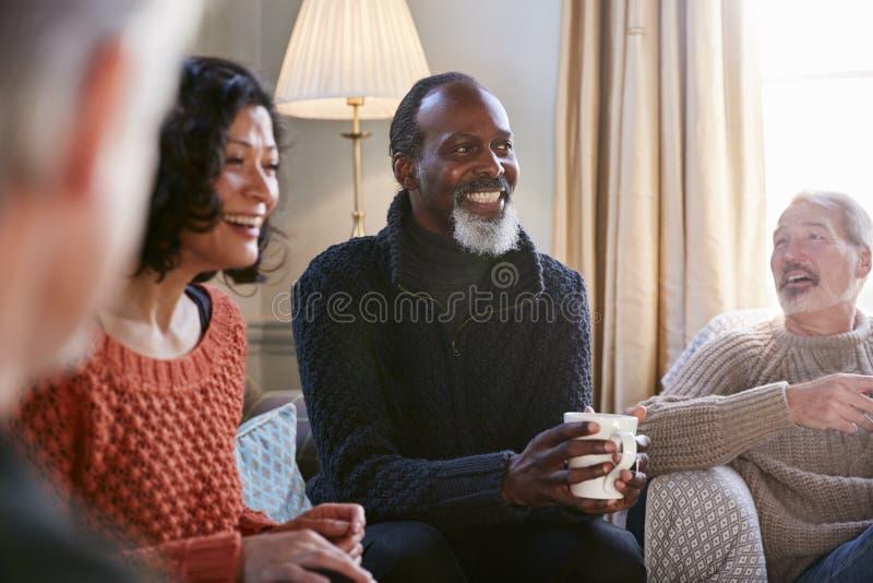 Amigos envelhecidos meio da reunião dos pares em torno da tabela na cafetaria imagens de stock royalty free