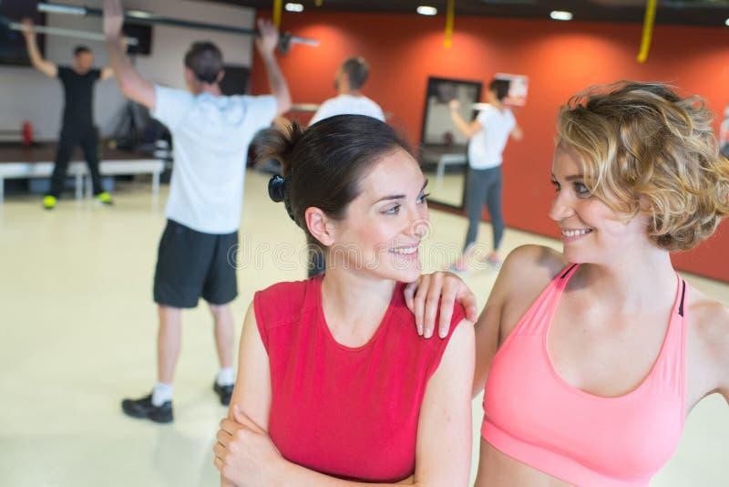 Amigos fêmeas atléticos novos lindos no clube do gym imagem de stock royalty free