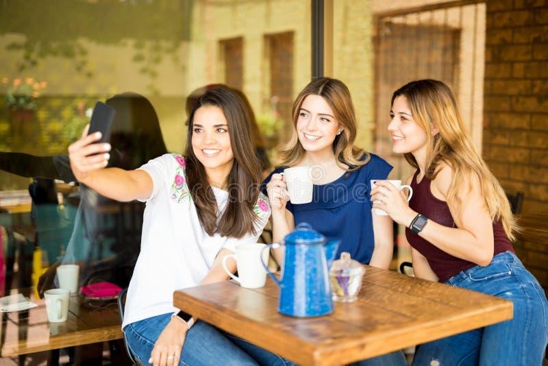 Amigos fêmeas bonitos que tomam o selfie no café imagens de stock