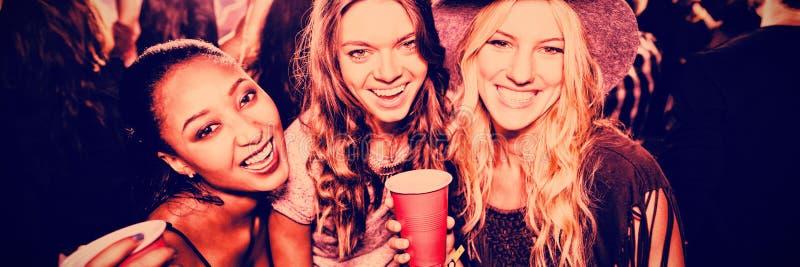 Amigos fêmeas com os copos descartáveis no clube foto de stock royalty free