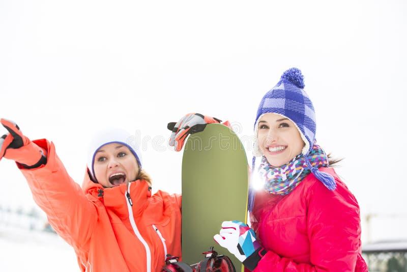 Amigos fêmeas entusiasmado com snowboard fora fotografia de stock