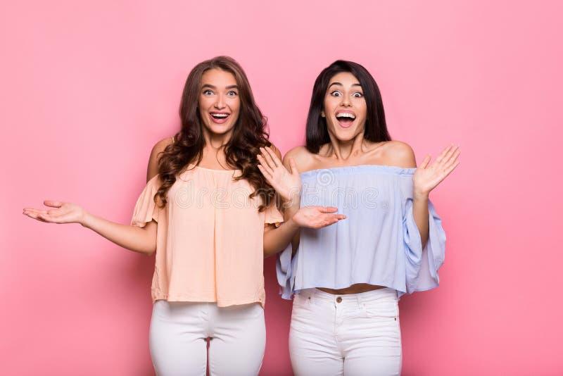 Amigos fêmeas entusiasmados que estão sobre o fundo cor-de-rosa foto de stock