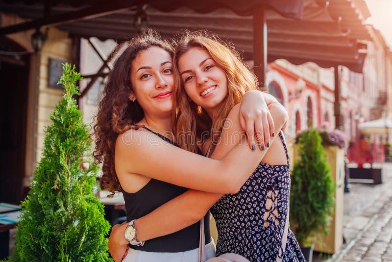 Amigos fêmeas felizes que abraçam na rua velha da cidade no verão Emoções reais dos melhores amigos das mulheres imagens de stock