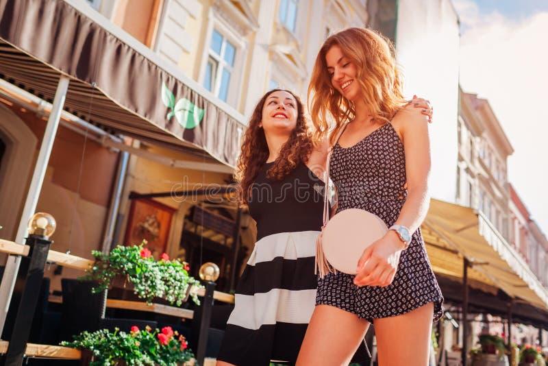Amigos fêmeas felizes que andam ao longo das ruas velhas da cidade no verão Refrigeração das meninas fotografia de stock