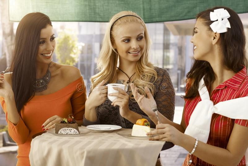 Meninas felizes que conversam no café exterior fotos de stock