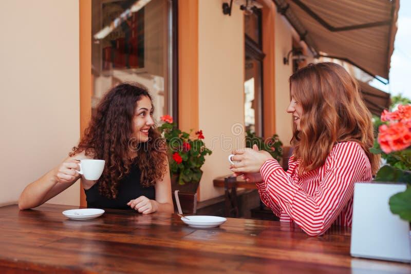 Amigos fêmeas felizes que comem o café no café exterior no verão Mulheres que conversam e que refrigeram ao ter bebidas na rua fotos de stock royalty free