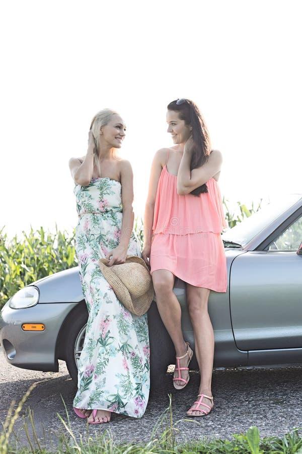 Amigos fêmeas felizes que conversam ao estar pelo convertible contra o céu claro imagem de stock
