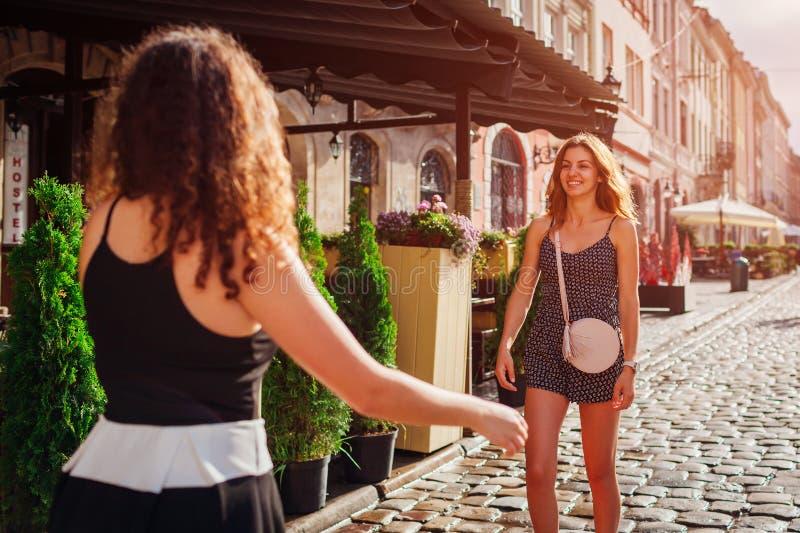 Amigos fêmeas felizes que encontram-se na rua Emoções reais das moças contentes de ver-se fotografia de stock