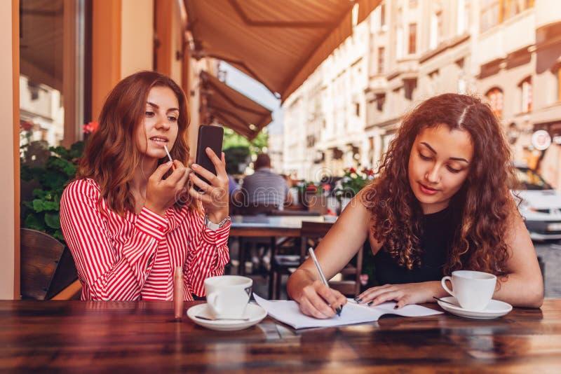 Amigos fêmeas felizes que fazem a composição ao comer o café e ao fazer trabalhos de casa no café exterior Universitárias que esc fotografia de stock royalty free