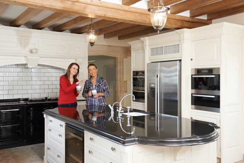 Amigos fêmeas maduros que estão luxo novo na cozinha cabida fotos de stock royalty free