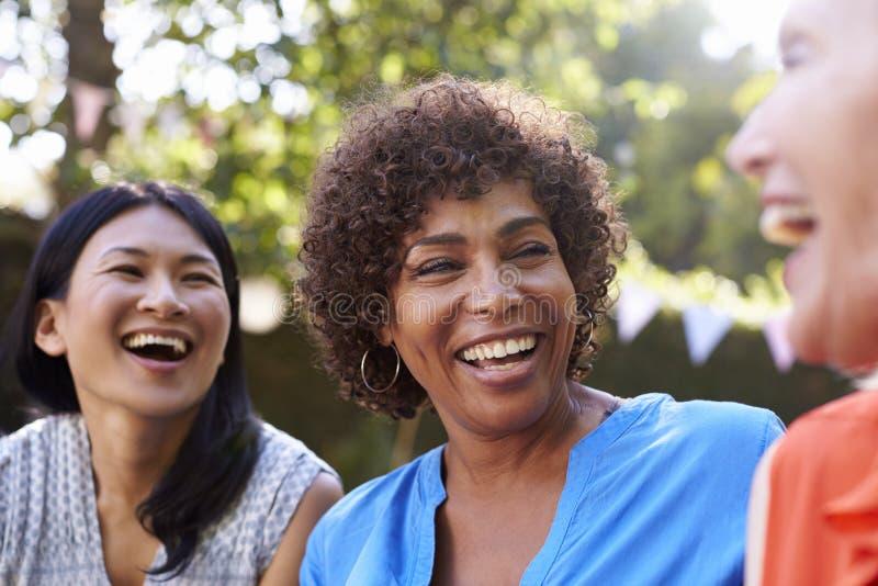 Amigos fêmeas maduros que socializam no quintal junto imagem de stock royalty free