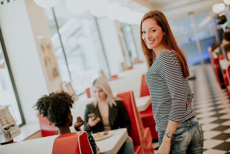 Amigos fêmeas multirraciais que comem o fast food em uma tabela nos di fotos de stock