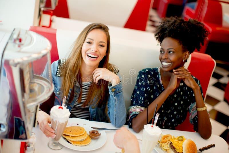 Amigos fêmeas multirraciais que comem o fast food em uma tabela nos di imagem de stock