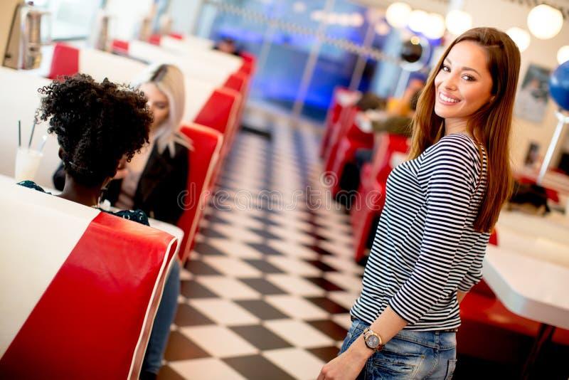Amigos fêmeas multirraciais que comem o fast food em uma tabela nos di fotografia de stock royalty free
