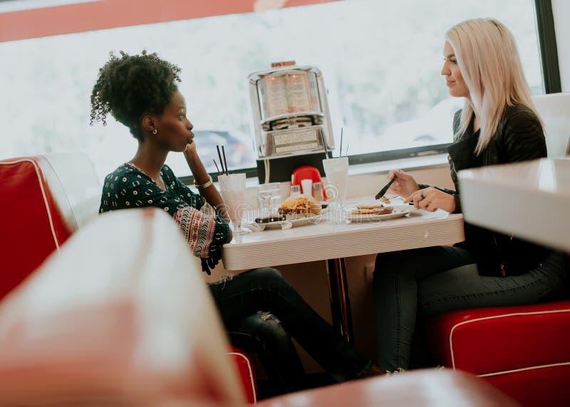 Amigos fêmeas multirraciais que comem o fast food em uma tabela nos di foto de stock