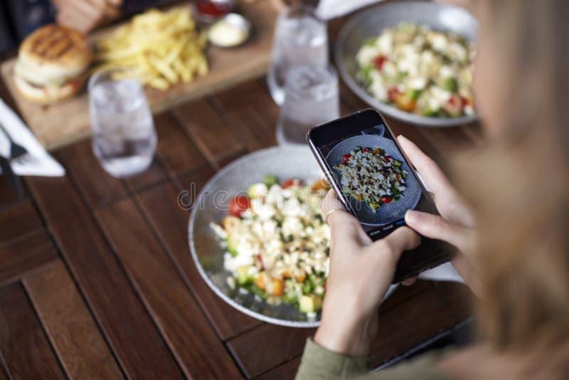 Amigos fêmeas no restaurante que toma a imagem do alimento no restaurante para afixar em meios sociais imagem de stock royalty free