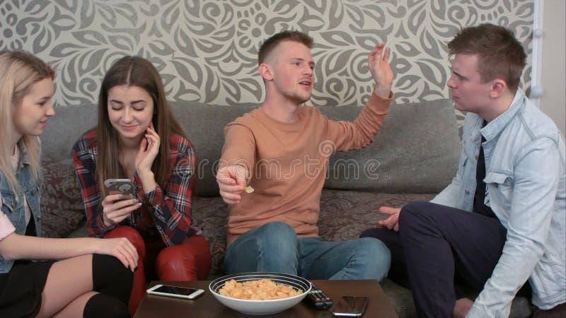 Amigos fêmeas novos ocasionais felizes que riem do que veem em um telefone celular, quando seus amigos masculinos falarem fotos de stock