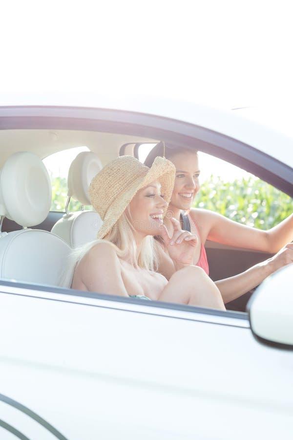 Amigos fêmeas novos que apreciam a viagem por estrada no carro no dia ensolarado fotos de stock royalty free
