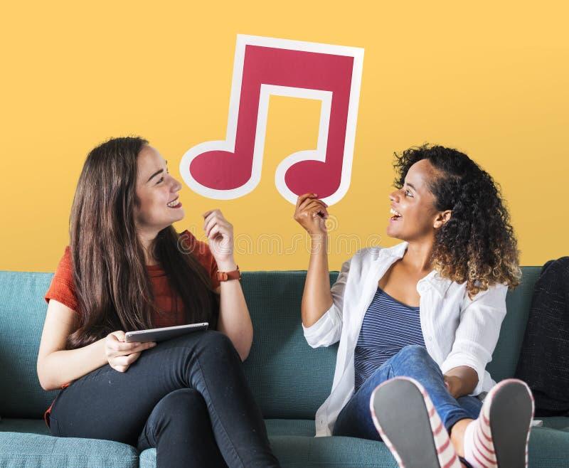 Amigos fêmeas novos que guardam um ícone da nota musical foto de stock royalty free