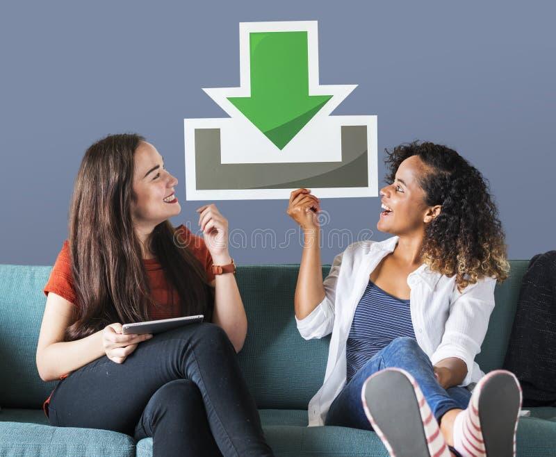 Amigos fêmeas novos que guardam um ícone da transferência imagens de stock