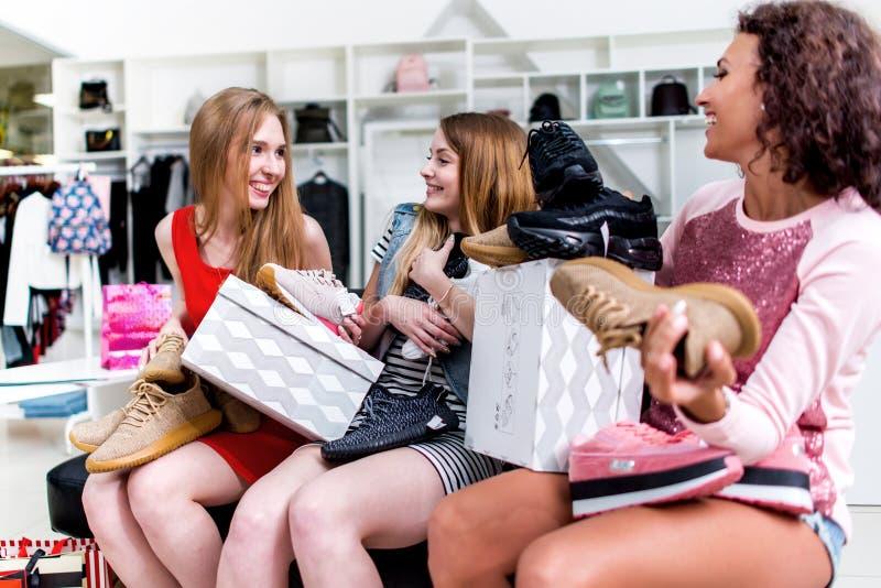 Amigos fêmeas positivos felizes com assento novo com sapatas e as caixas novas em seu regaço na loja da roupa fotografia de stock