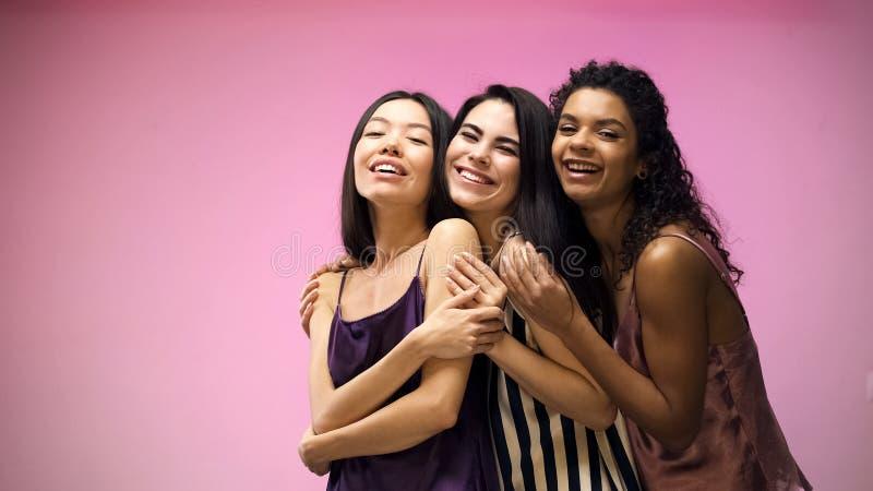 Amigos f?meas que abra?am e que levantam para a c?mera no fundo cor-de-rosa, partido de pijama fotografia de stock