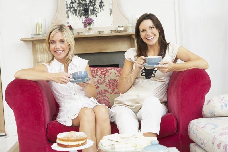 Amigos fêmeas que apreciam o chá e o bolo em casa imagens de stock royalty free