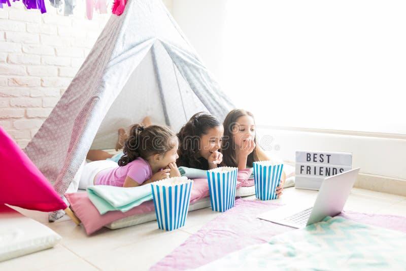 Amigos fêmeas que apreciam petiscos ao olhar o portátil na barraca fotografia de stock royalty free