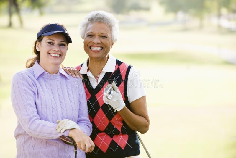 Amigos fêmeas que apreciam um jogo do golfe fotografia de stock