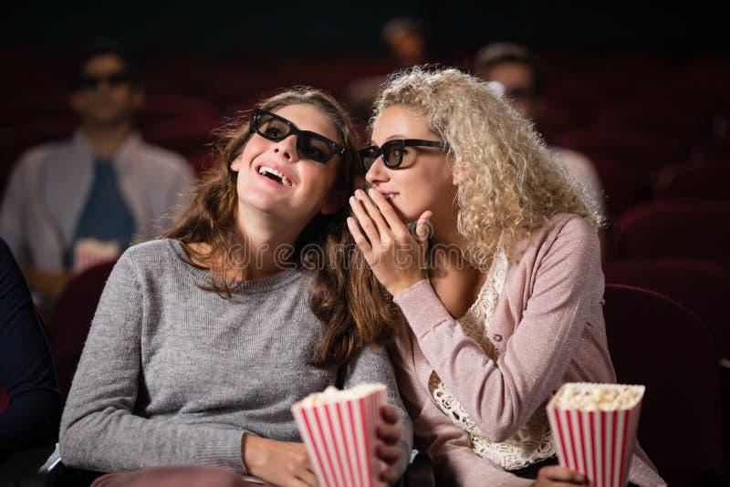 Amigos fêmeas que bisbilhotam ao olhar o filme fotos de stock royalty free