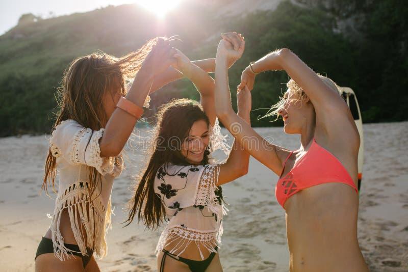 Amigos fêmeas que dançam na praia e que têm o divertimento imagem de stock