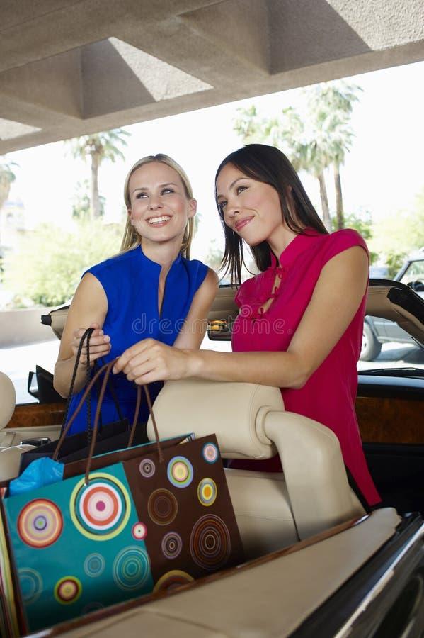 Amigos fêmeas que guardam sacos de compras foto de stock royalty free