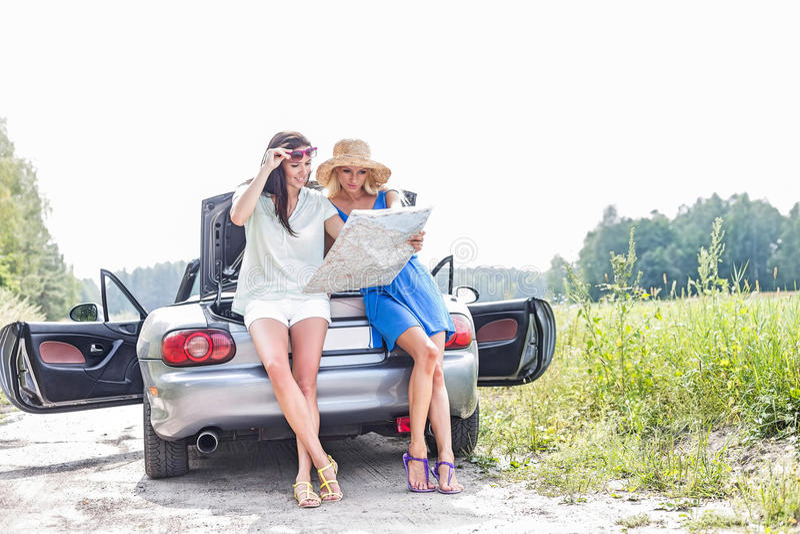 Amigos fêmeas que leem o mapa ao inclinar-se no convertible fotografia de stock royalty free