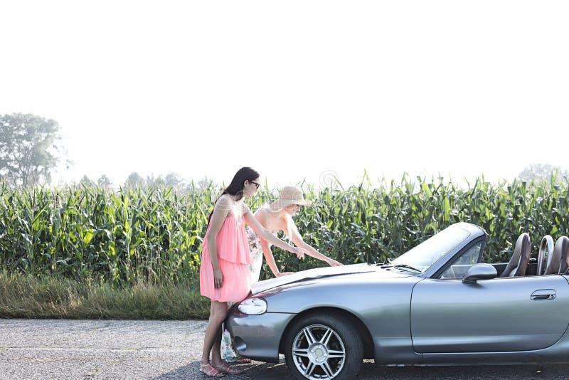 Amigos fêmeas que leem o mapa no convertible contra o céu claro fotografia de stock