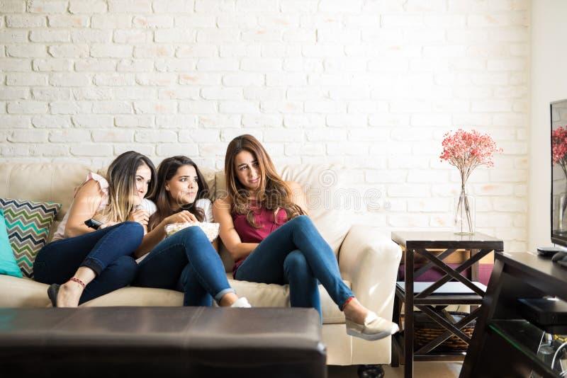 Amigos fêmeas que olham um filme de terror foto de stock