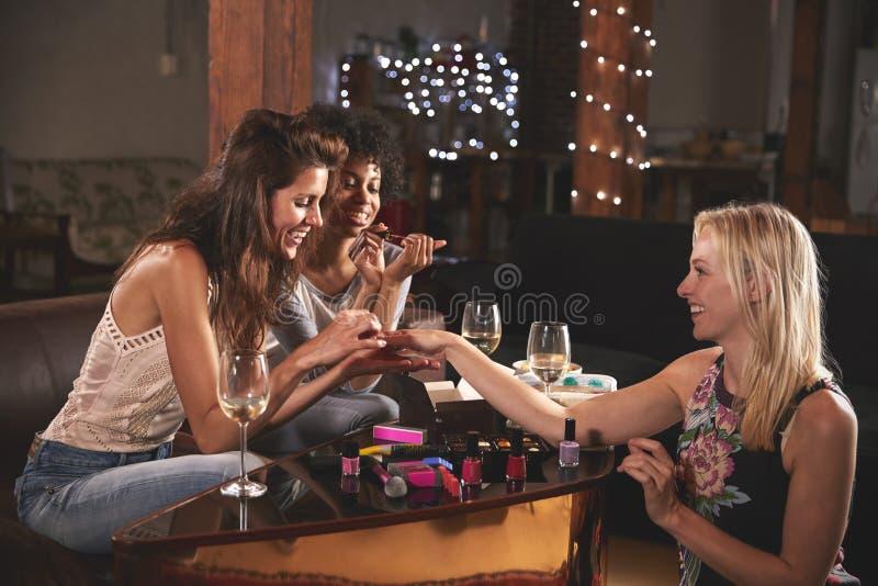 Amigos fêmeas que penduram para fora e que fazem seus pregos em casa fotografia de stock royalty free