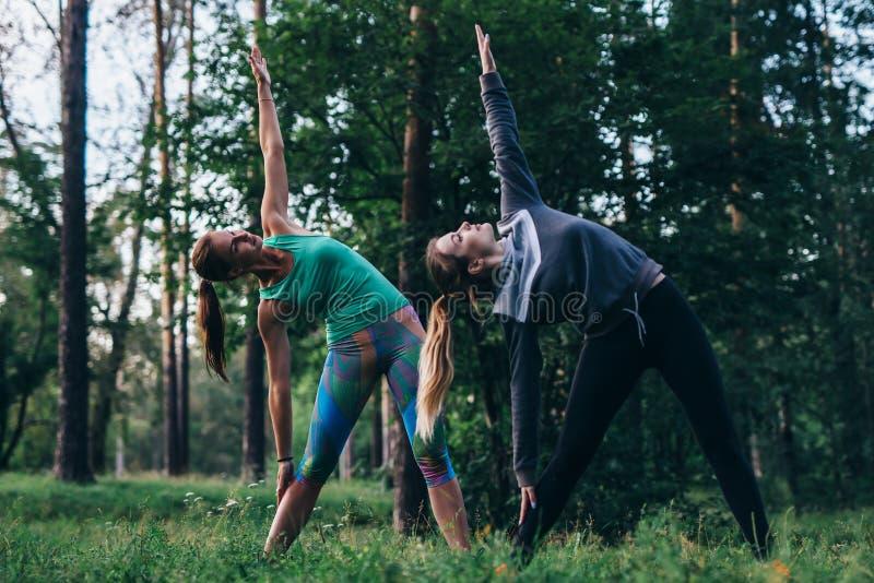 Amigos fêmeas que praticam a ioga que faz fora a pose lateral ereta da curvatura ou do triângulo no parque imagens de stock royalty free