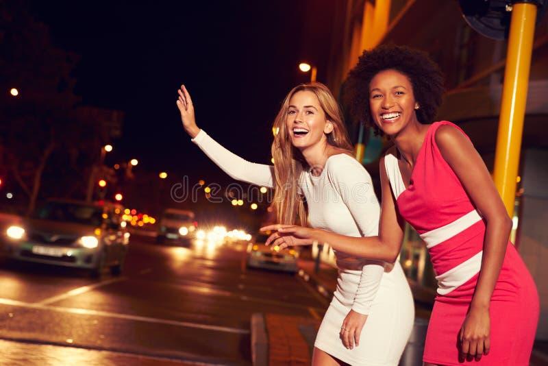 Amigos fêmeas que saudam o táxi na rua da cidade na noite foto de stock royalty free