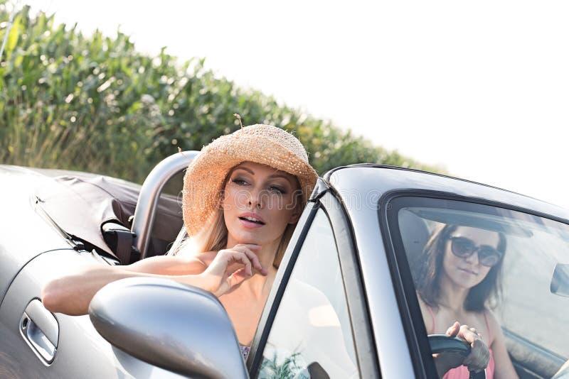 Amigos fêmeas que sentam-se no convertible no dia ensolarado fotografia de stock