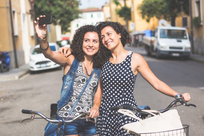 Amigos fêmeas que tomam um selfie com suas bicicletas imagens de stock royalty free