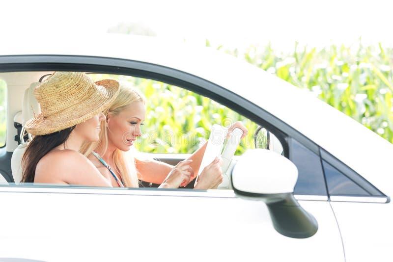 Amigos fêmeas que usam a tabuleta digital no carro imagem de stock