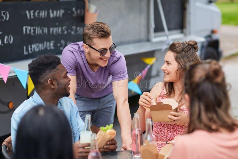 Amigos felices con las bebidas que comen en el camión de la comida fotografía de archivo