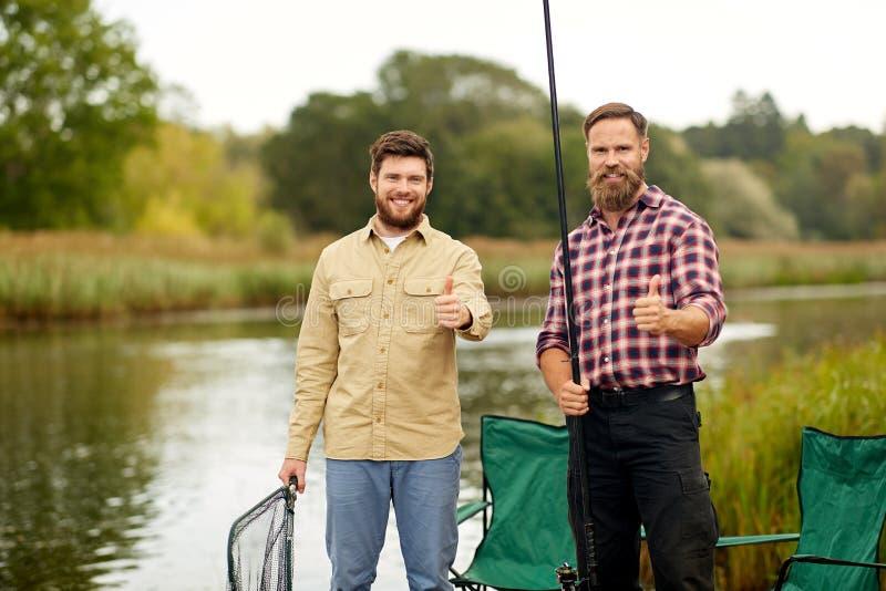 Amigos felices con las cañas de pescar que muestran los pulgares para arriba fotos de archivo