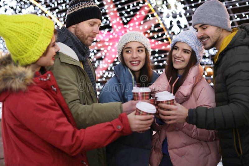 Amigos felices con las tazas de vino reflexionado sobre en el invierno imagen de archivo libre de regalías