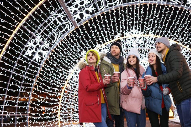 Amigos felices con las tazas de vino reflexionado sobre en la feria del invierno fotos de archivo