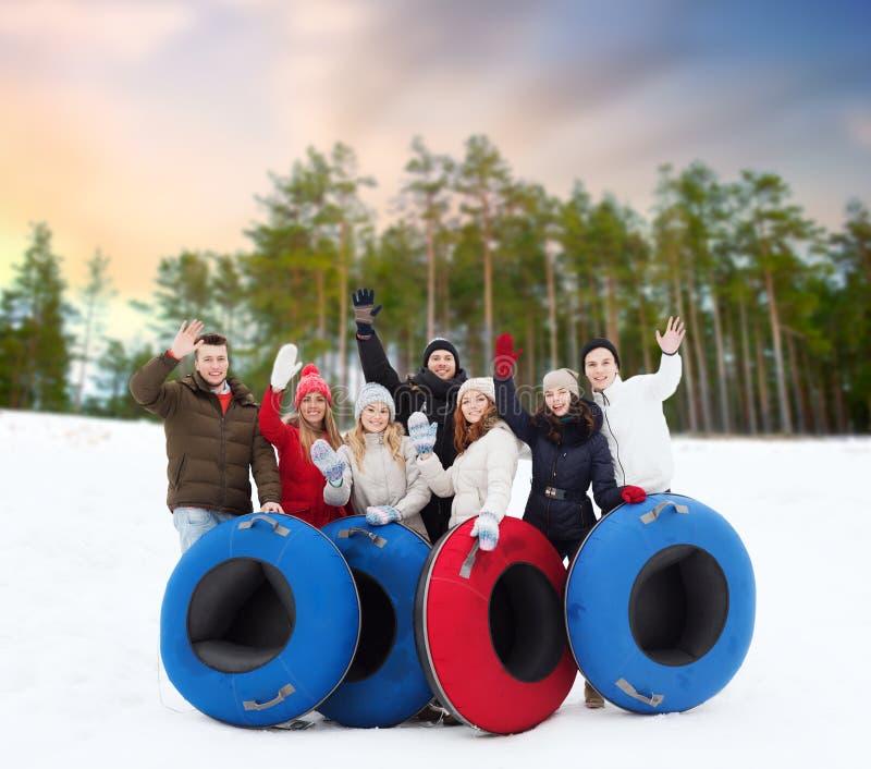 Amigos felices con los tubos de la nieve al aire libre en invierno fotos de archivo libres de regalías
