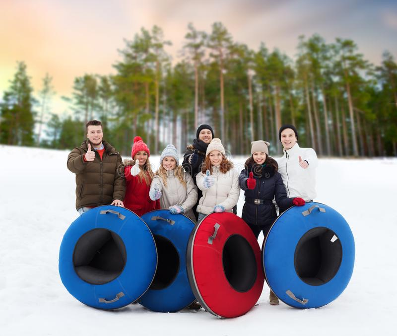 Amigos felices con los tubos de la nieve al aire libre en invierno foto de archivo